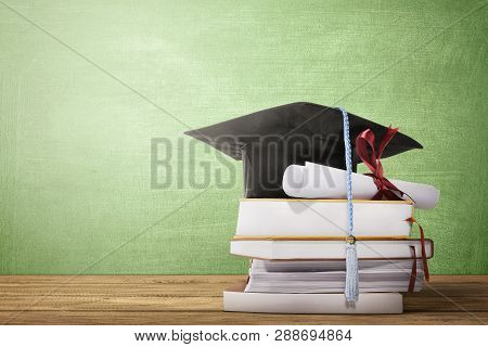 Graduation Hat, Diploma Scroll And Books On The Wooden Table With Chalkboard Background