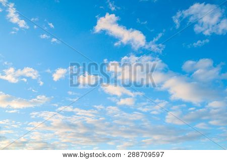 Sky background. Blue sky landscape with dramatic sundown clouds lit by evening sunset light - evening sky view. Colorful sky landscape, sunny sky with picturesque clouds .Vast sky background