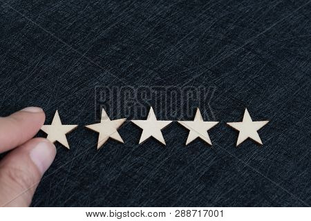 Hand Putting 5 Stars On Dark Texture Black Background With Copy Space Using As Customer Experience,