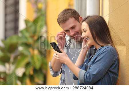 Happy Couple Sharing Earphones To Watch Media On Smart Phone In A Colorful Street