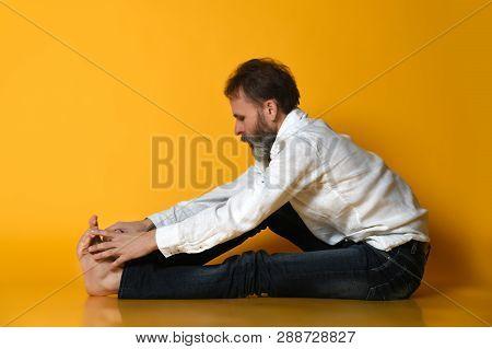 Sporty Fit Old Man In Jeans Practices Ashtanga Vinyasa Yoga Back Bending Asana Paschimottanasana - S