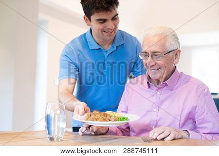 Male Care Assistant Serving Meal To Senior Male Seated At Table