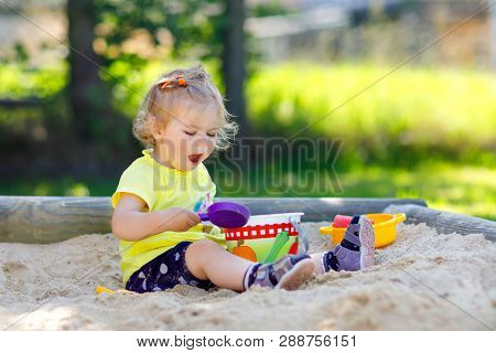 Cute Toddler Girl Playing In Sand On Outdoor Playground. Beautiful Baby Having Fun On Sunny Warm Sum