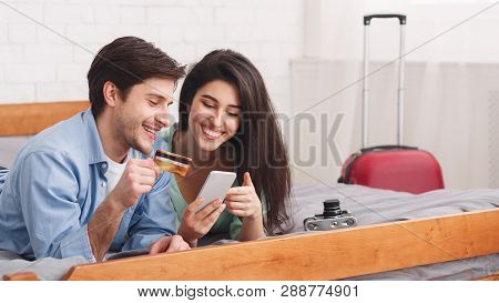 Loving Couple Booking Tickets Using Phone And Credit Card, Ready For Travel