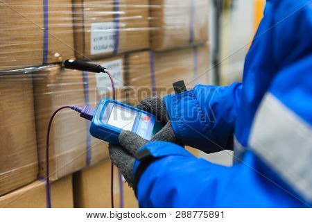 Hand of worker using thermometer to temperature measurement in the goods boxes with ready meals after import in the cold room or warehouse for keep temperature room