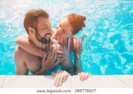 Cheerful Youthful Guy And Lady Resting While Swimming Pool Outdoor. Couple In Water