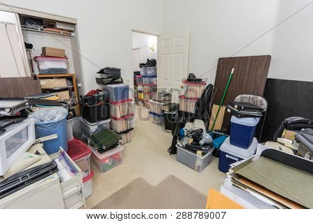 Messy back office with boxes, clutter old equipment and miscellaneous storage.