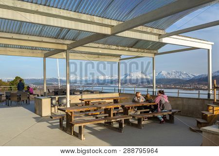 Alesund, Norway - April 13, 2018: People resting at the view point of beautiful Alesund town in Norway. Alesund is a town and municipality in west Norway.