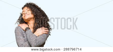 Young beautiful woman with curly hair wearing grey sweater Hugging oneself happy and positive, smiling confident. Self love and self care