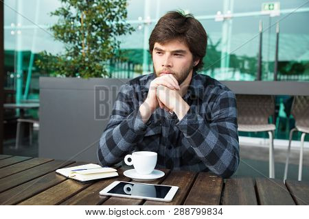 Sad Student Sitting In Cafe After Failure On Exam. Gloomy Young Man In Casual Shirt Sitting In Stree