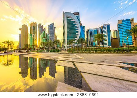 Scenary Of Doha West Bay Skyline At Sunset Light Reflecting In The Water Of Park In Downtown. Modern