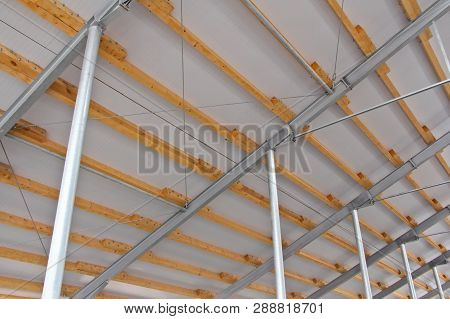 Wooden Beams On A Metal Frame. Construction Of Agricultural Buildings. The Construction Of The Barn
