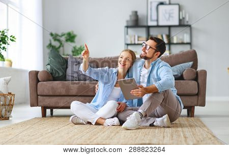 Concept Of Moving, Buying  Home.  Young Married Couple Plans To Repair And A Project Apartment