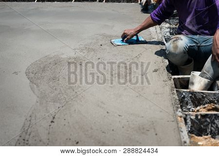 Plasterer Concrete Cement Work. Mason Leveling The Floor. Using A Plastic Square Trowel For Smooth O