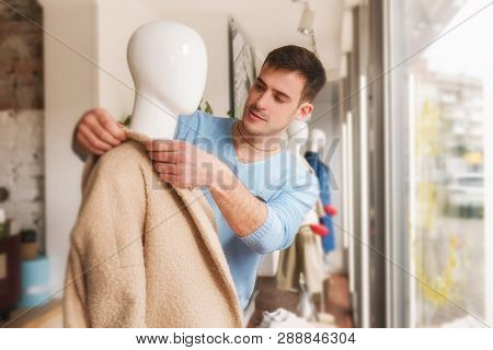 Man Putting Clothes On A Mannequ In Store.