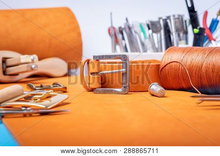 Leather Working Or Leather Craft. Orange Colored Or Tanned Leather On Leather Craftmans Work Desk .