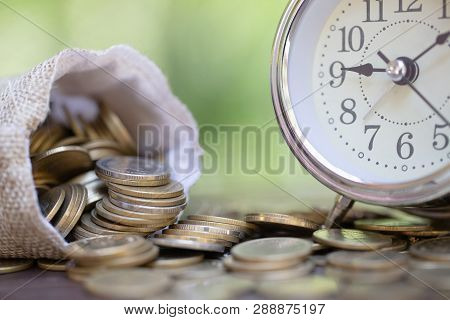 Money Bags And Alarm Clock On Wooden Table With Nature Background,  Money Savings, Investment, Growi