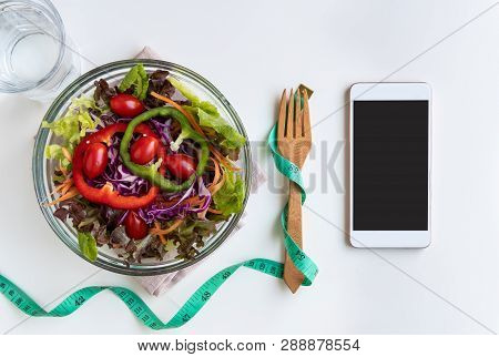 Fresh Salad With Measuring Tape And Empty Screen Smartphone On White Background. Diet, Healthy Eatin