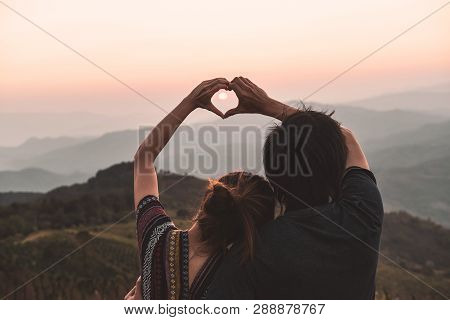 Loving Young Couple Making A Heart Shape With Hands And Looking Beautiful Landscape At Sunset