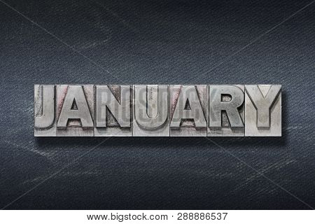 January Word Made From Metallic Letterpress On Dark Jeans Background