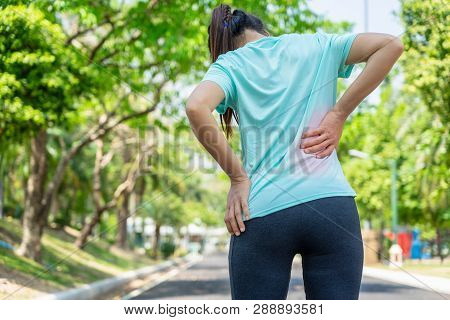 Young Asian Woman On Running Road In The Park Having A Back Pain.