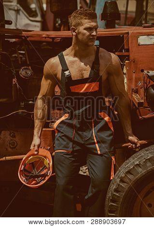 Worker Concept. Strong Worker Rest At Heavy Construction Machine. Handsome Worker In Working Uniform