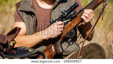 Hunter Man. Hunting Period. Male With A Gun, Rifle. Man Is Charging A Hunting Rifle. Close Up. Proce