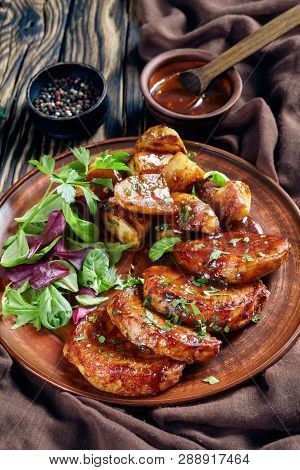 Grilled Sticky Glazed Pork Cutlets With Baked Potatoes Served With Fresh Green Salad On Earthenware
