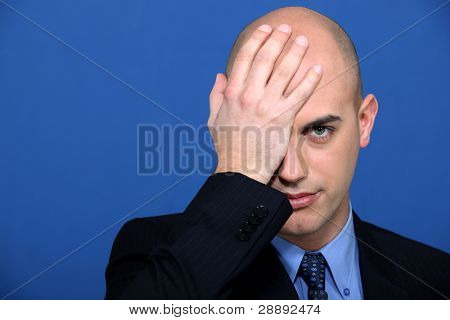 Businessman holding his hand to his face