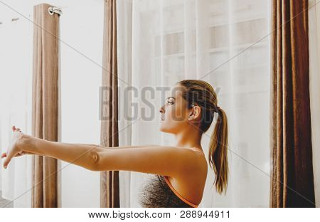Young woman is stretching out near window in home. Fitness lifestyle.