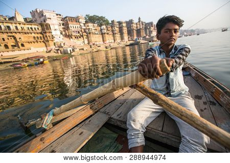 VARANASI, INDIA - MAR 26, 2018: Boatmen on a boat glides through water on Ganges river along shore of Varanasi. According to legends, the city was founded by God Shiva about 5000 years ago.