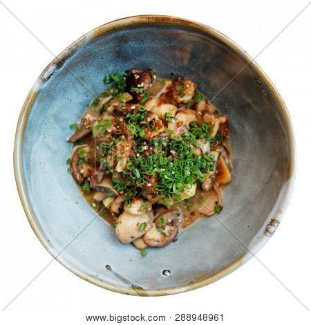 Teppanyaki fried mushrooms with green leek in earthenware bowl, isolated on white background