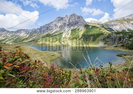 Beautiful And Idyllic Mountain Landscape Scenery: Mountain Range, Lake With Clear Water, Flowers And