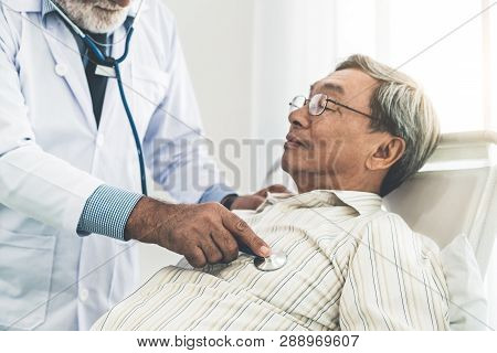 Mature Doctor And Senior Patient In Hospital Ward.