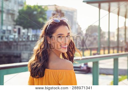 Happy latin woman looking behind while walking on street. Beautiful young woman enjoying vacation during summer. Cheerful girl in smart casual walking and looking at camera while smiling.