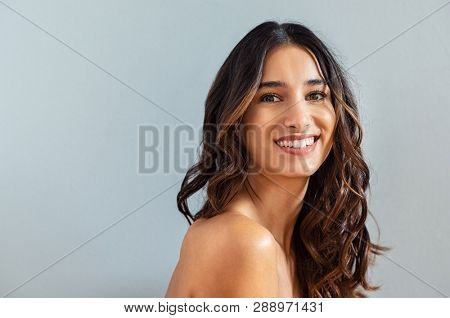 Smiling young woman looking at camera isolated on gray background. Beauty portrait of brunette girl with long curly hair looking at camera. Skin care treatmet and haircare concept at beauty spa.