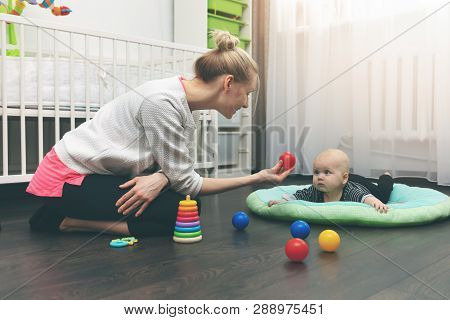 Babysitting - Nanny Playing With Little Baby On The Floor At Home