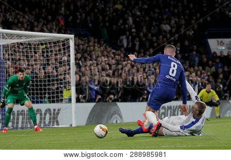 LONDON, ENGLAND - MARCH 7 2019: Ross Barkley of Chelsea is tackled by Mykyta Burda of Dynamo Kiev during the Europa League match between Chelsea and Dynamo Kyiv at Stamford Bridge.