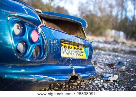 The Back Bumper Of An Old Wrecked Sports Car At The Abandoned Furber's Scrapyard In Shropshire, Engl