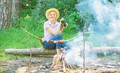 Woman tourist holds binoculars while sits on log near bonfire. Observing nature concept. Girl enjoy hike in forest observing nature. Her hobby is ornithology. Girl ornithology expedition in forest poster