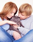 happy young couple on the bed at home with their cat poster