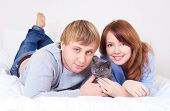 happy young couple on the bed at home with their cat (focus on the woman) poster