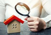 A woman is holding a magnifying glass over a wooden house. Real estate appraiser. Assessment of the condition of the house. Property valuation / appraisal. Search for housing and apartments. poster