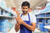 Hypermarket or supermarket indian male employee touching sprained wrist as physical effort pain concept poster