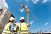 Construction engineers discussion with architects at construction site or building site of highrise building poster