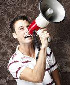 portrait of young man shouting with megaphone against a vintage wall poster