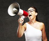 portrait of middle aged woman shouting using megaphone against a grunge wall poster