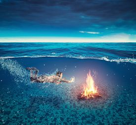 Young Woman Swims Underwater To A Camp Fire. Split Image - Half Under Water Half Above Water.