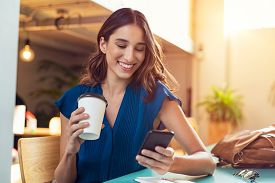 Young beautiful woman holding coffee paper cup and looking at smartphone while sitting at cafeteria. Happy university student girl using mobile phone. Businesswoman drinking coffee and smiling.