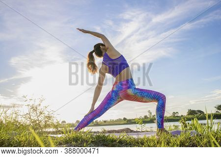 Portrait Of Gorgeous Young Woman Practicing Yoga With Nature Background.